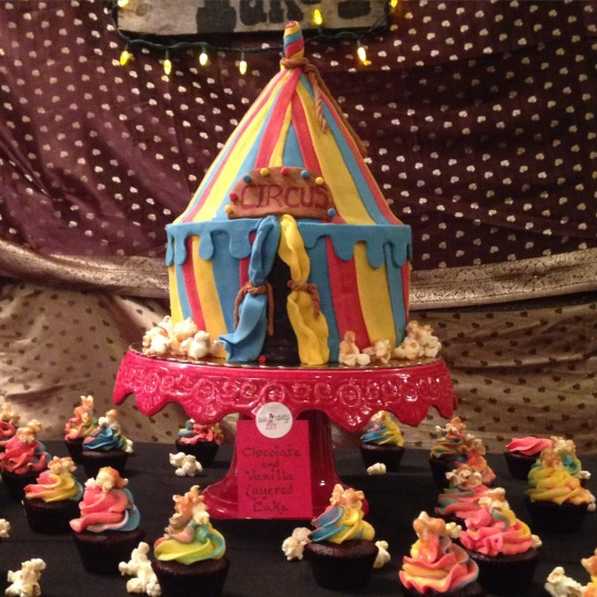 Circus themed women's center fundraiser party. chocolate and vanilla circus tent cake with chocolate and vanilla cupcakes with salted caramel popcorn on top.