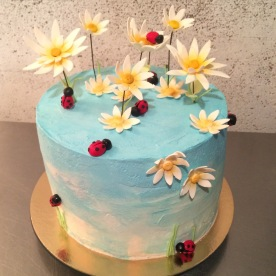 Gluten free vanilla cream cake with blue sky buttercream and gum past daisies and ladybugs