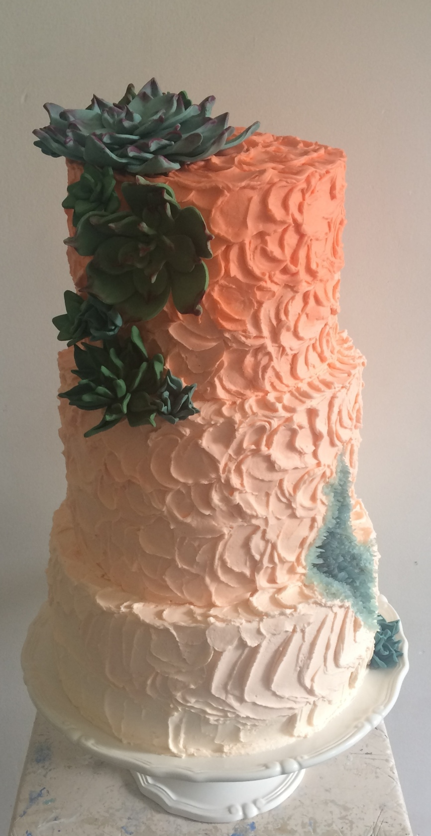 Geode and succulent wedding cake with peach ombre buttercream icing