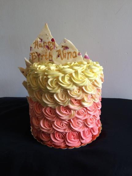 Lemon raspberry cake with lemon curd raspberries lemon buttercream ombre roses and white chocolate with dried raspberries and rose petals.