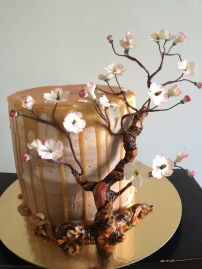 Gluten free chocolate salted caramel cake with a fondant tree and gun past blossoms