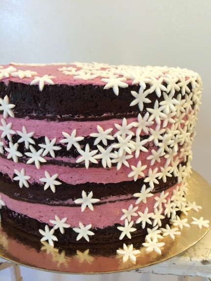 Chocolate blackberry naked wedding cake with little white fondant flowers.