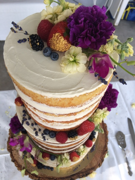 Three teared vanilla mixed berry naked wedding cake, filed with mixed berry compote, vanilla whip cream with fresh flowers, fresh berries and vanilla buttercream.