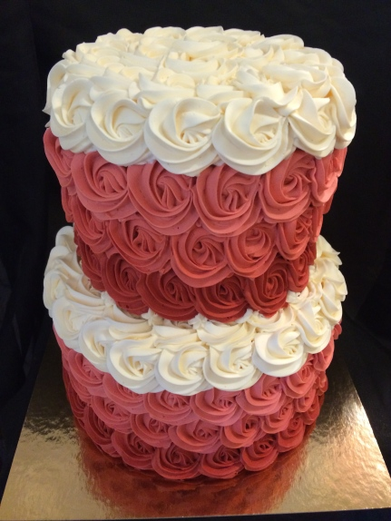 Red velvet wedding cake with red, pink, and white buttercream roses