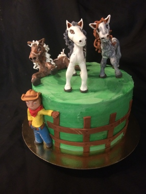 Horses and cowboy cake. Lemon raspberry cake with green buttercream and handmade fondant horses and cowboy