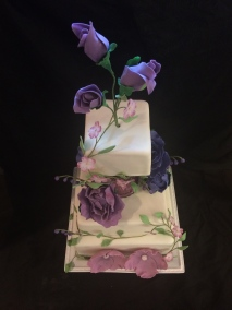 Handmade purple flower wedding cake with a glass spacer