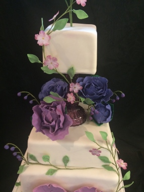 Handmade purple flower wedding cake with a glass spacer