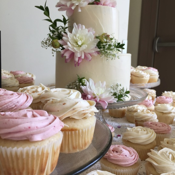 Simple white buttercream cake with fresh flowers cake matching cupcakes