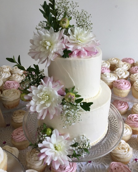 Simple white butter cream cake with fresh flowers and matching cupcakes