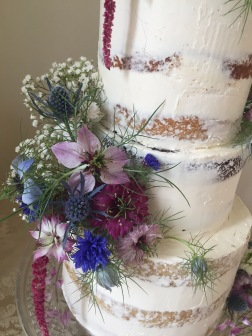 Half naked wedding cake with fresh flowers