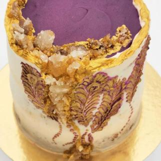 Geode sugar crystal cake with buttercream peacock feathers